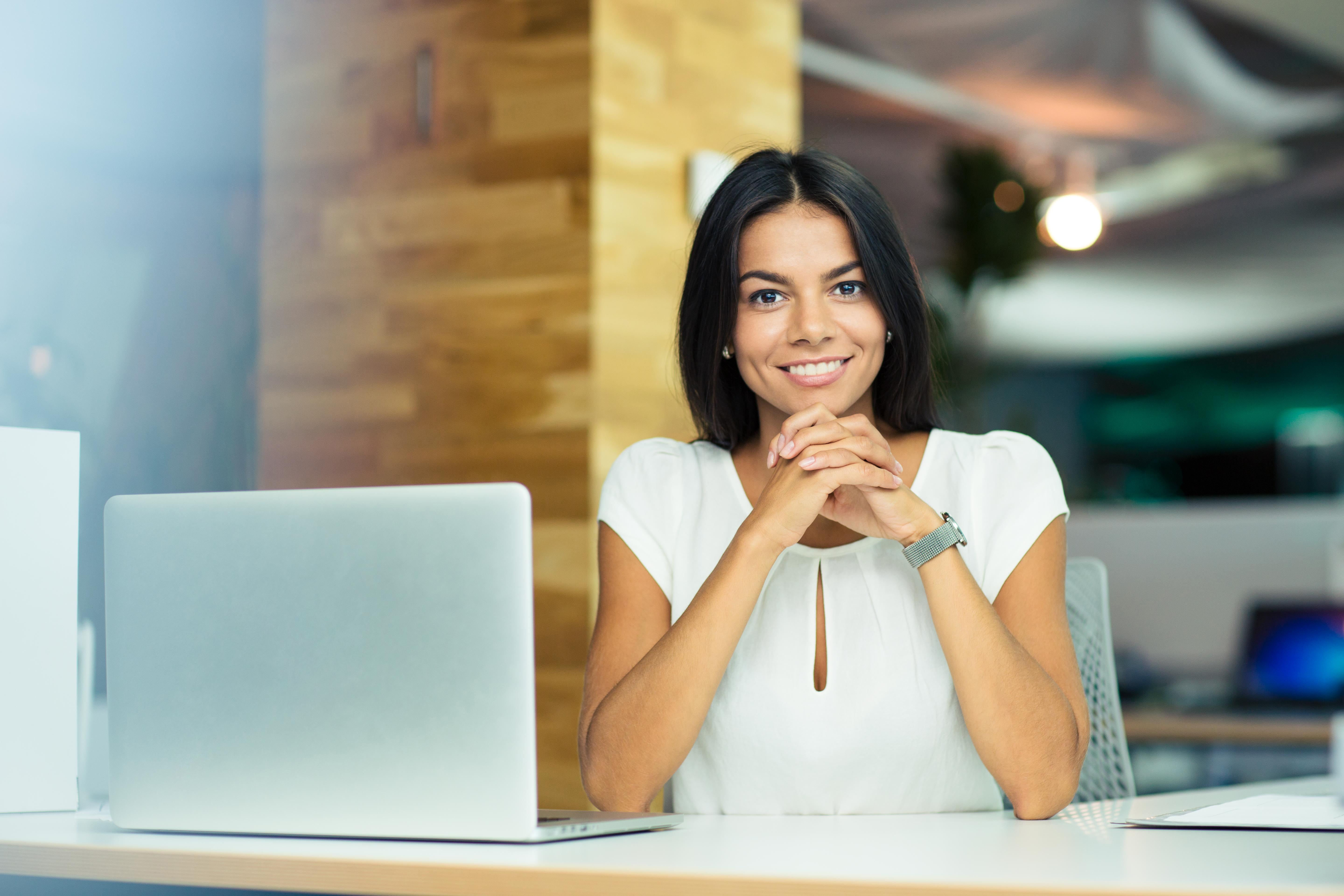 Portrait of a cheerful businesswoman sitting at the table in office an