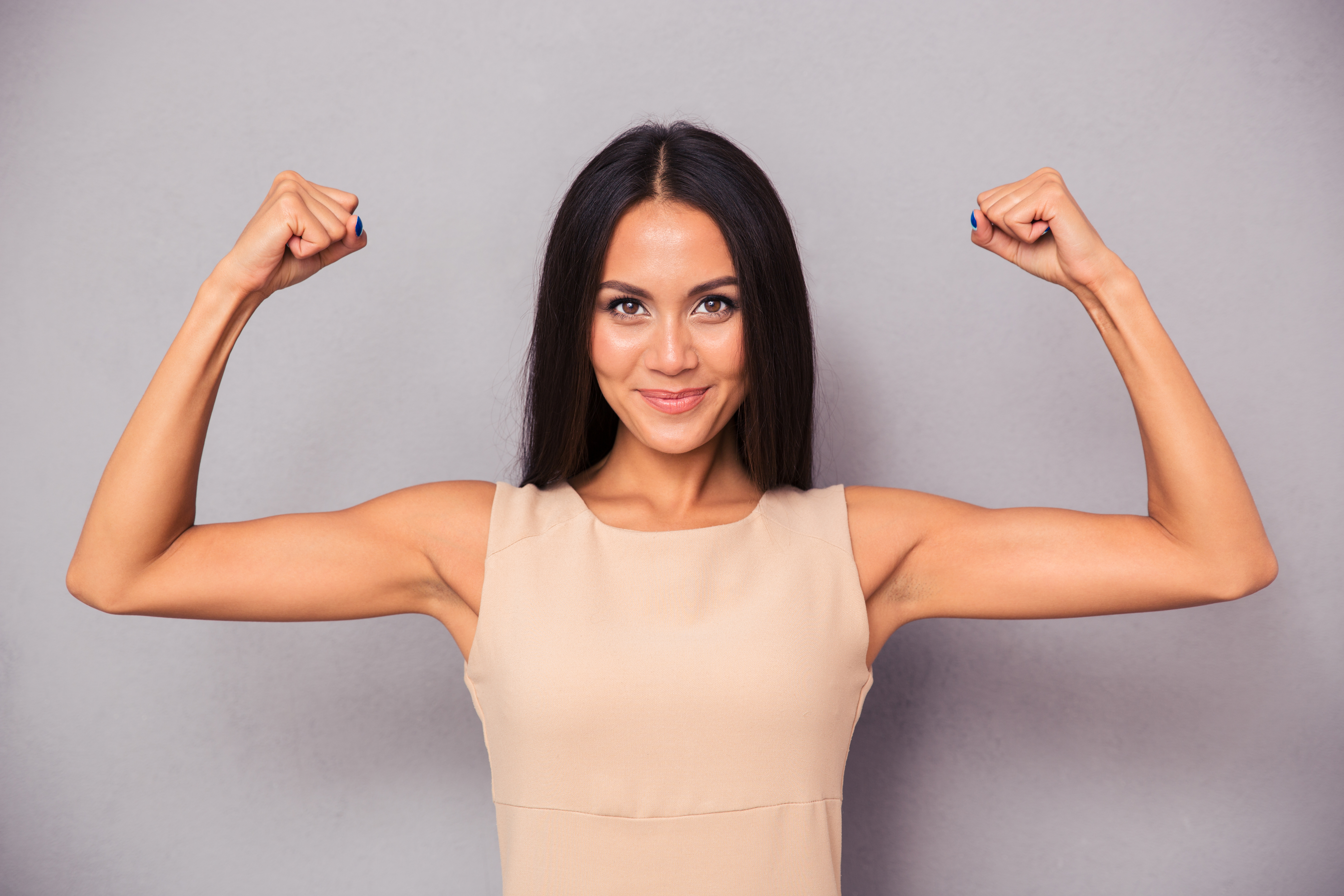 Portrait of a happy elegant woman showing her biceps on gray backgroun